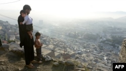 A man stands in front of his home in the hillside neighborhood of Jamal Mina high above Kabul.