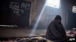 Një migrant rri ulur në një kamp për refugjatë në Beograd