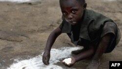 БҰҰ-ның WFP бағдарламасының төгілген ұнын теріп отырған бала. Конго, 15 қараша 2008 жыл.