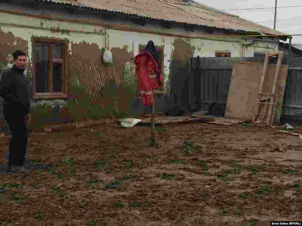 Житель Атырау Адилет Жолдыгулов показывает свой дом, к которому подбирается вода.