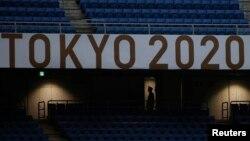 Član osoblja nosi zaštitnu masku na praznom međunarodnom stadionu u Jokohami tokom fudbalskog meča između Obale Slonovače i Saudijske Arabije, Japan, 22. juli 2021.