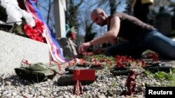 A protester places models of Russian tanks and soldiers on a recently installed monument to fallen soldiers at the Olsany Cemetery in Prague on March 21.