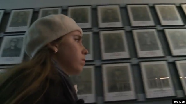 "Yevgenia Karatygina in front of portraits of Holocaust victims in a still from the trailer for the documentary ""Holocaust -- Wallpaper Paste?"""
