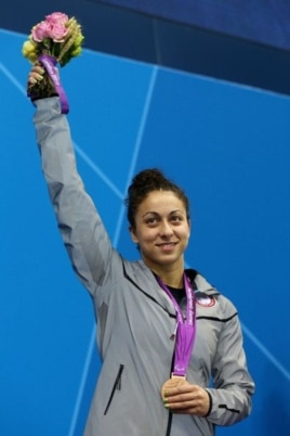Elizabeth Stone shows off some of her hardware at the Olympic Park Aquatics Center in London.