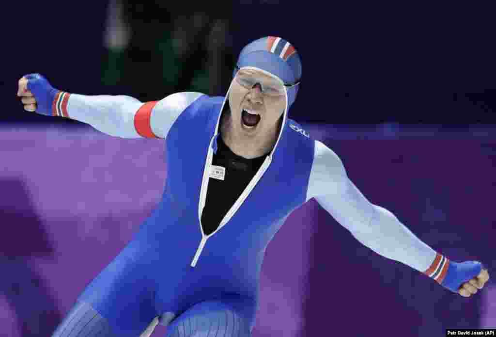 Бег на коньках: золотой медалист Хавард Лорентцен из Норвегии празднует установление нового олимпийского рекорда во время гонки на 500 метров