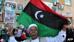 A Libyan man holds his new national flag aloft during celebrations in the eastern coastal city of Benghazi.