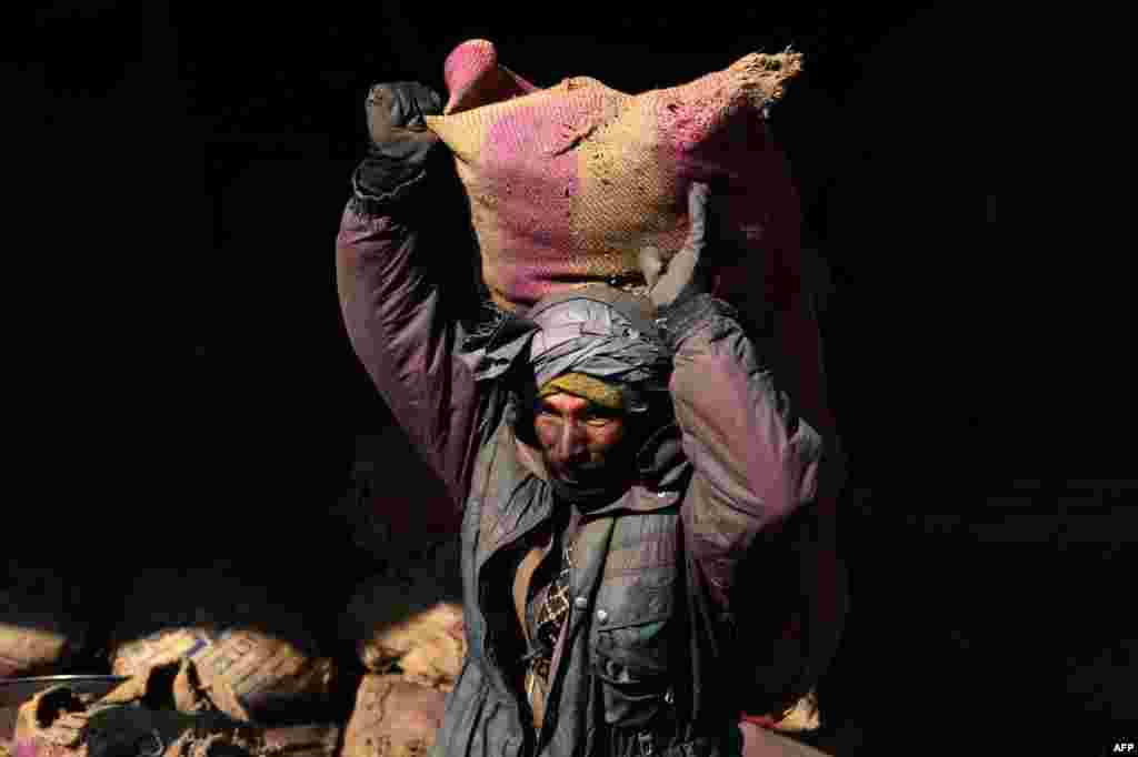 An Afghan laborer carries a sack of coal over his shoulder at a coal yard in Herat. (AFP/Aref Karimi)