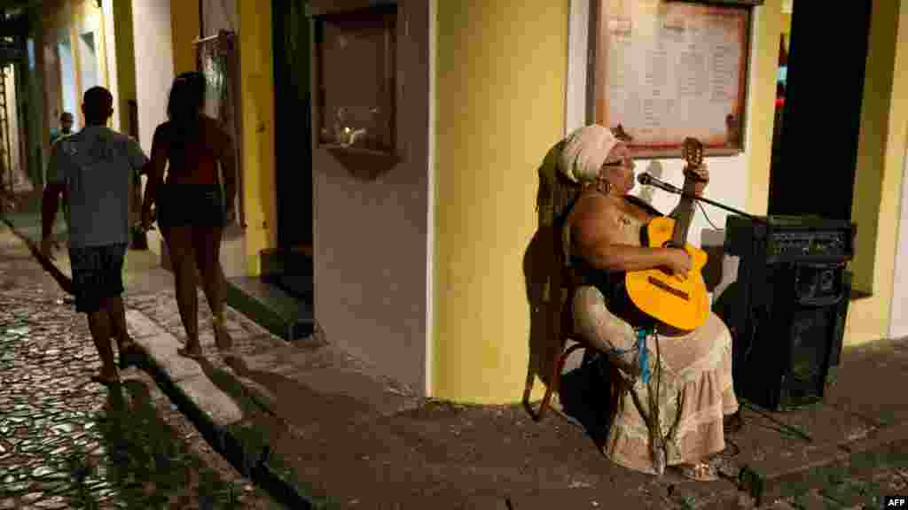 "A woman sings while playing guitar in Salvador's historic center during Dia do Samba (""Samba Day"") on December 2. (AFP Photo/Yasuyoshi Chiba)"