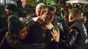 Turkey -- A police officer arrests and grabs the throat of an employee of Bugun newspaper and Kanalturk TV during a protest in Istanbul against the government's crackdown on media. Oct. 28, 2015.