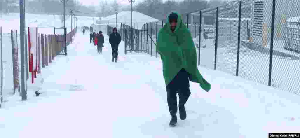 Migrants walk through the snow at the Lipa camp.Some live in squats in the woods around Bihac.