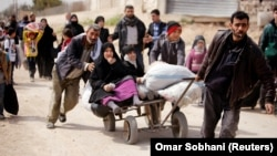 People flee the rebel-held town of Hammuriyeh on March 15.