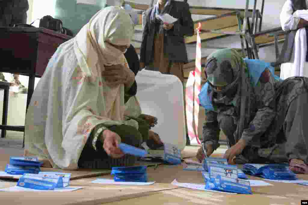 Workers with the Afghan Independent Election Commission count ballots at a polling station for the presidential elections in Kandahar on April 5.