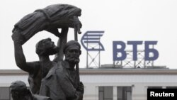 Russia -- Part of a monument to Soviet state founder Vladimir Lenin is seen against a sign for VTB Bank in Stavropol, January 22, 2015