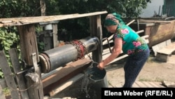 Сарытөбе ауылының тұрғыны Мария Мұсабаева құдықтан су алып жатыр. Бұл құдықты тұрғындардың өздері ақша жинап, қазып алған. 30 шілде 2019 жыл.