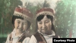 Childhood photo of filmmaker Janyl Jusupjan (left) with her sister Salima wearing traditional Kyrgyz clothing made by their mother.