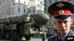 Rossiyalik politsiyachi G'alaba paradi hozirligida ishtirok etayotgan Topol-M qit'alararo ballistik raketasi oldida turibdi, Moskva, 2008 yil 5 mayi.