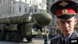 A Russian policeman stands in front of a Topol-M ICBM during a rehearsal for the Victory Day parade in Moscow in May 2008.
