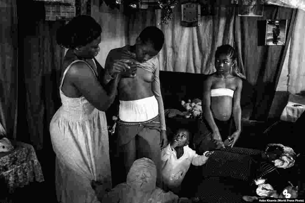 """Номинация: """"Современный проблемы"""". Фоторепортаж Эту фотографию сделала египетский фотограф Хеба Хамис. На нем 28-летняя Вероника массирует грудь своей 10-летней дочери Мишель в восточном Камеруне. Это распространенная традиционная практика, которая, как считается, может приостановить развитие девочки, что защитит ее от изнасилований и домогательств."""