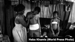 Камерундук 28 жаштагы Вероника 10 жаштагы кызы Мишелдин көкүрөгүн ушалап жатат. Камерундуктар бул ыкма кыздарды зомбулуктан сактайт деп ишенишет. Египеттик сүрөтчү Хеба Хамистин бул эмгеги 2018-жылдагы эң мыкты сүрөттөрдүн бири болду.