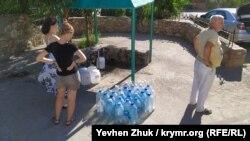 Люди набирають воду з артезіанської свердловини в селі Верхньосадове, вересень 2020 року