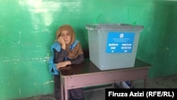 An election commission worker sits next to an empty ballot box in a women's voting center in Kabul on September 28.