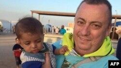 آلن هنینگ با کودکی در یک اردوگاه پناهندگان در مرز ترکیه و سوریه