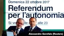Ілюстрацыйнае фота. Лідэр партыі Forza Italia Сільвіё Бэрлюсконі паказвае сыстэму для галасаваньня разам з прэзыдэнтам Лямбардыі Рабэрта Мароні падчас прэс-канфэрэнцыі аб рэфэрэндумах у Міляне, 18 кастрычніка 2017 году