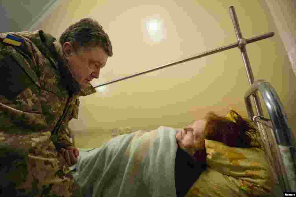 Президент України Петро Порошенко (ліворуч) розмовляє з жінкою, яка постраждала під час обстрілу Краматорська з установок «Град» російськими гібридними силами, 11 лютого 2015 року