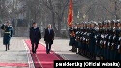 Gyrgyzystanyň täze we öňki prezidentleri Sooronbaý Jeenbekow (ç) we Almazbek Atambaýew (s) täze döwlet baştutanynyň wezipä geçiş dabarasynda, 24-nji noýabr, 2017.