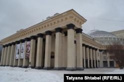 Фасад здания театра с непонятными черными вставками на колоннах