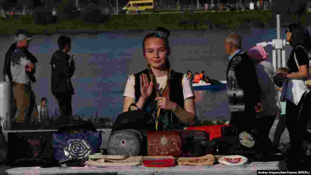 A girl sells handbags in traditional designs.
