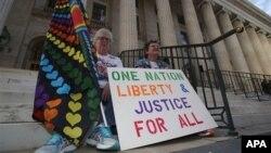 Памела Филе и ее супруга Лорин Фортмиллер участвуют в акции в поддержку однополых браков на ступенях здания суда в Денвере