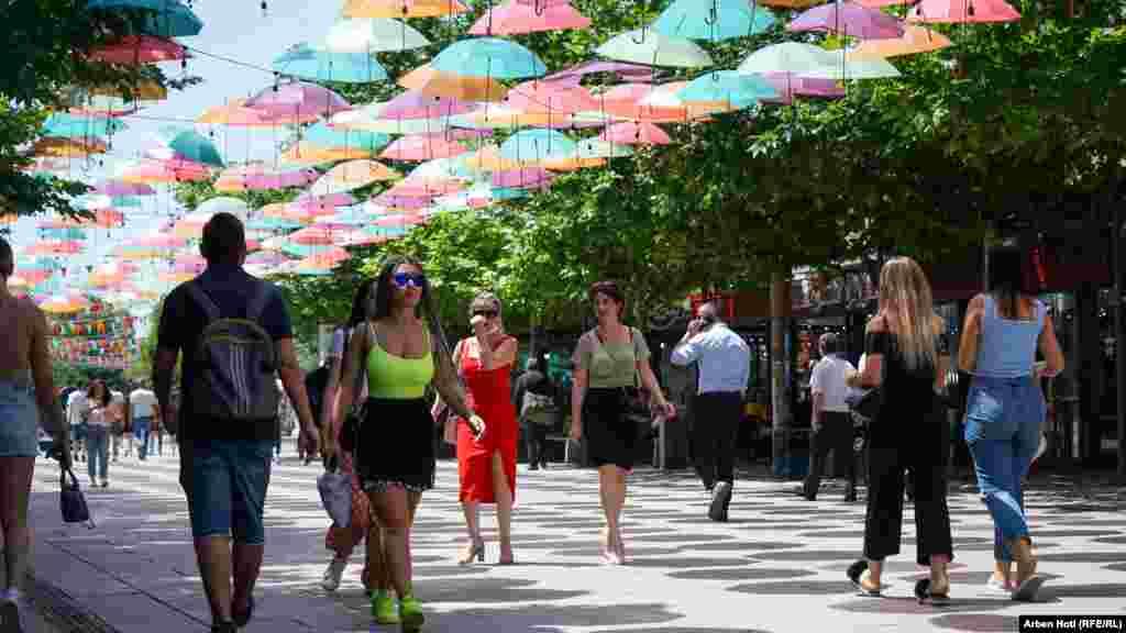 Qytetarët ecin në shesh mes temperaturave të larta në kryeqendrën e Kosovës.