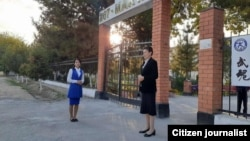 Teachers wait outside the gate of a school in the Tashkent region early on October 4.