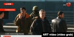 """Reshat Ametov (right) stands near a masked Russian soldier and a man wearing a red armband typical of the so-called """"self-defense"""" forces shortly before the Crimean activist's abduction in March 2014."""