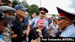 A woman shouts at police during a rally in Almaty, June 9, 2019.