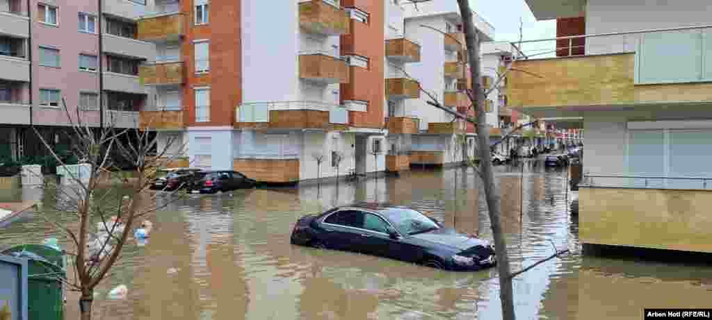 Një veturë e mbuluar pothuajse nga uji shihet pranë një kompleksi banesor në Komunën e Fushë Kosovës.
