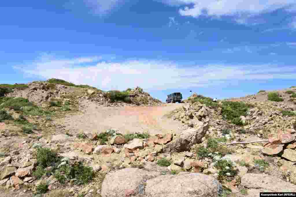 Водитель внедорожника, поднявшегося вверх по ущелью, во время стоянки на вершине охлаждает перегревшийся двигатель.