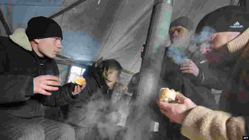 Homeless people eat a hot meal and drink tea in one of the newly opened tent shelters in the western Ukrainian city of Lviv.