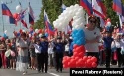 Мәскеу аннексиялаған Қырым түбегінде өткен шараға Ресей туын ұстап шыққан адамдар. Симферополь, 1 мамыр 2018 жыл.