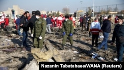 FILE PHOTO: Security officers and Red Crescent workers are seen at the site where the Ukraine International Airlines plane shot down after take-off from Iran's Imam Khomeini airport, on the outskirts of Tehran, Iran January 8, 2020.