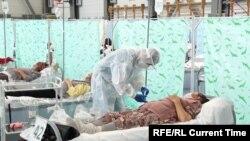 Медик в защитном костюме оказывает помощь пациенту в одном из временных стационаров. 2020 год.