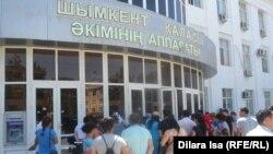 Шымкент қалалық әкімдігі алдында жер телімін алуға өтініш беруге келген тұрғындар. 25 мамыр 2016 жыл.