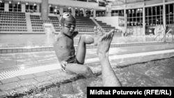 Disabled Bosnian swimmer Ismail Zulfic gives his trainer a high-five