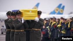 Soldiers carry a coffin containing the remains of one of the 11 Ukrainian victims of the Ukraine International Airlines Flight 752 plane disaster during a memorial ceremony at the Boryspil International Airport outside Kyiv on January 19.