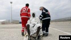 Сотрудники итальянского Красного Креста помогают беженцу, доставленному в сицилийскую гавань Аугуста, 31 мая 2015 г.