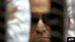 د مصر دولتي ټیلي ویژن د حسني مبارک دا انځور وښود چې په کې دی د خپلې فیصلې له پاره عدالتي کوټه کې ناست دی.