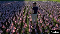 File photo a woman stands among some of the 3,000 flags placed in memory of the lives lost in the September 11, 2001 attacks, at a park in Winnetka, Illinois.