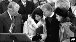U.S. Secretary of State Cyrus Vance (left) and U.S. President Jimmy Carter comfort Mary Anne Dubs, the widow of slain Ambassador Adolph Dubs, as Dubs' body is returned to Andrews Air Force Base outside Washington, D.C., on February 18, 1979.