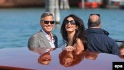 Киноактер Джордж Клуни (сол жақта) қалыңдығы Амал Аламуддинмен. Венеция, Италия, 26 қыркүйек 2014 жыл.